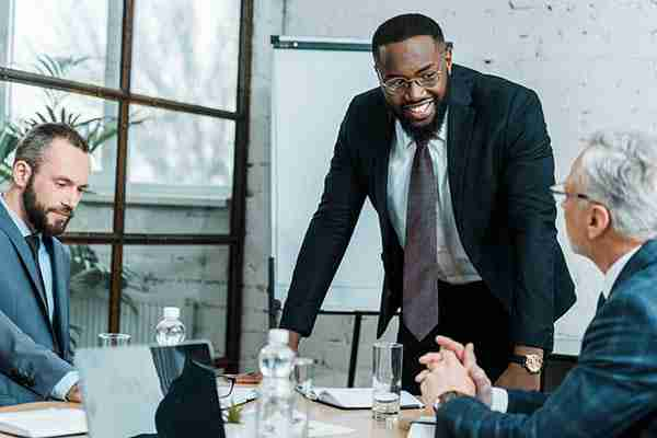 selective focus of cheerful african american business coach smiling near coworkers